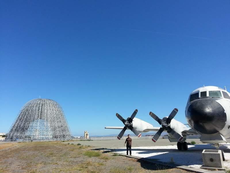 """Сергей Петров пред тренажор за пилоти в базата на НАСА """"Еймс"""" в Калифорния. Конструкцията вляво е хангар, който преди се е използвал за поправка на дирижабли."""