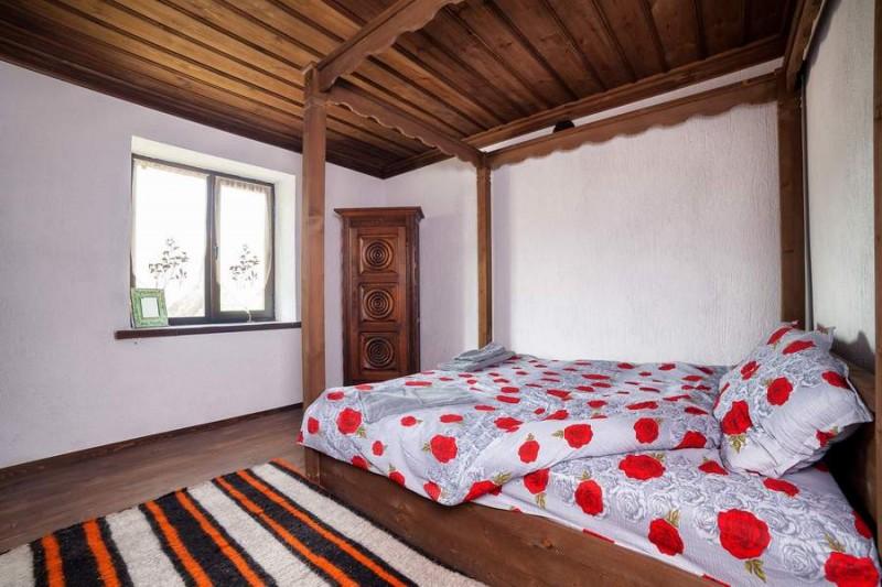 Спалнята в първата къща. Тук, както навсякъде, има родопски таван. Дървеното легло е правено от местни майстори. Шкафът е от Париж, в бретонски стил, с типичната украса с кръгли орнаменти.