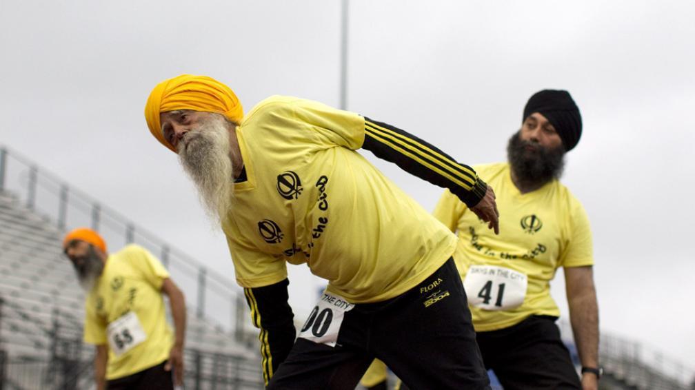 Стогодишният бегач Фауджа Сингх (в средата) загрява с колеги преди състезание. Той е със световен рекорд на 100, 200, 400, 800 и 1500 м.