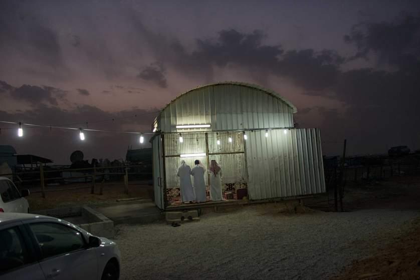 Саудитски мъже се молят в павилион на пазар за камили.