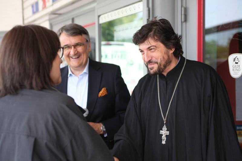 Собственичката на кино Elbe г-жа Янцен поздравява отец Григорий след прожекцията на филма.