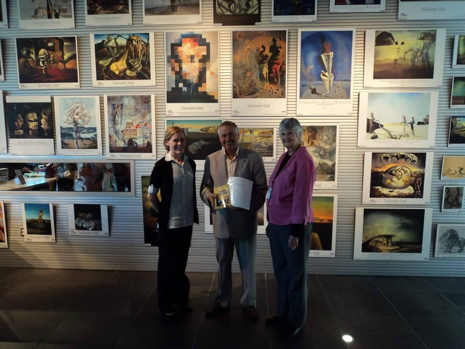"""Преводачът на стихосбирката """"Извън циферблата"""" Слав Данев предава превода на директора на музея Дали в Сейнт Питърсбърг, Флорида г-жа Каръл Бътлър (вдясно) и главния библиотекар на библиотеката към музея."""